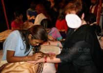 in einem Pavillon werden allen Frauen die Hände und Füße bemalt