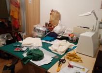Der Zuschneidetisch, hinten zugestellt mit Stricksachen, im hellen Schrank Kostüme